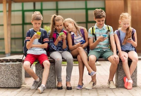 Kinder sitzen mit Smartphone auf einer Bank