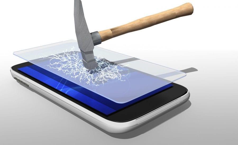 Schutzfolie auf einem Smartphone wird mit Hammer geschlagen