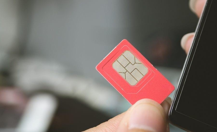 Person hält rote Sim Karte in der Hand