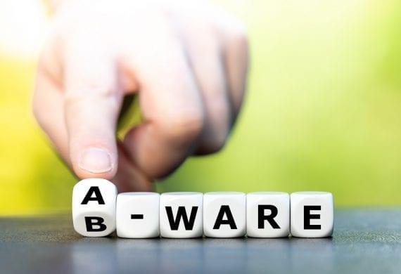 """Hand dreht Würfel und ändert den Ausdruck """"B-Ware"""" in """"A-Ware""""."""